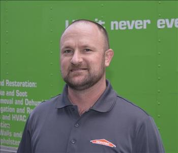 Male employee with beard wearing a gray shirt with a green background.