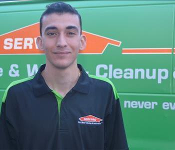 Male employee with black and green SERVPRO shirt with a green background.