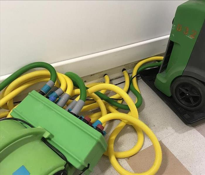 Yellow and green tubes from a drying system with a green dehumidifier close by