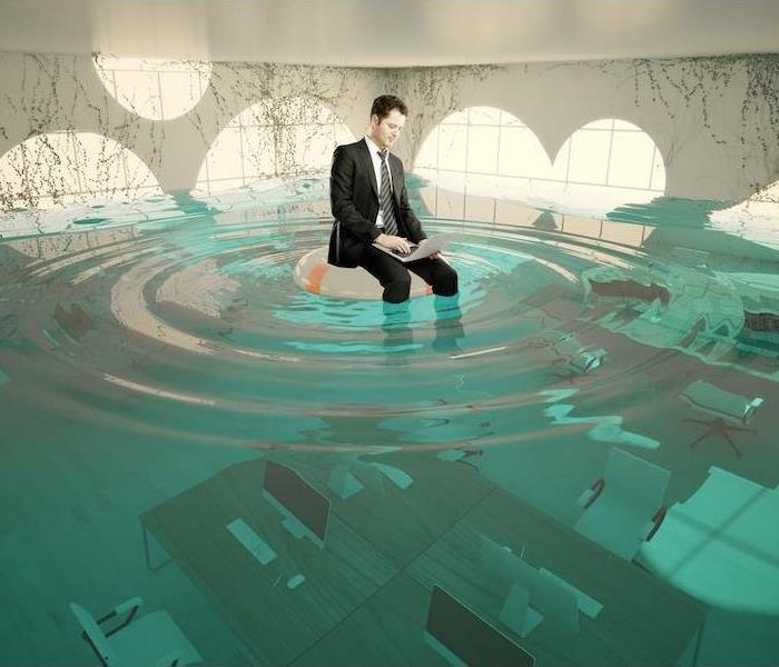 Businessman with laptop sitting on lifebuoy in abstract flooded office interior