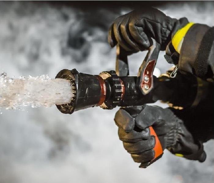 fireman discharging water from fire hose